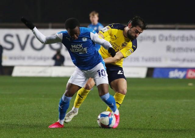 Siriki Dembele of Peterborough United battles with Elliott Lee of Oxford United. Photo: Joe Dent/theposh.com.