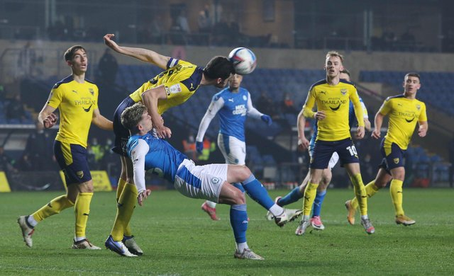 Sammie Szmodics of Peterborough United is beaten to the ball by Elliott Moore of Oxford United. Photo: Joe Dent/theposh.com.