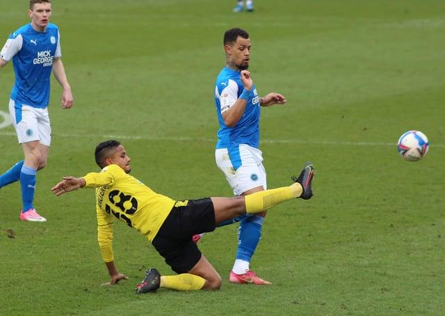 Jonson Clarke-Harris of Peterborough United challenges for the ball with Michael Mancienne of Burton Albion. Photo: Joe Dent/theposh.com.