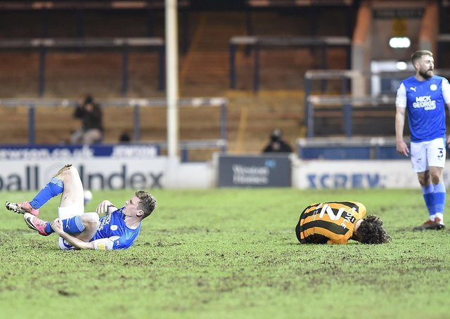 Posh midfielder Ethan Hamilton (right) has just clattered into Lewie Coyle of Hull, a challenge that would lead to a red card. Photo: David Lowndes.