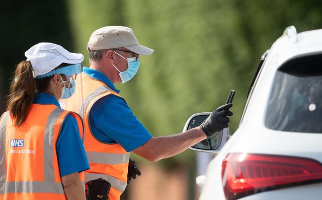 Staff scan the barcode on a coronavirus test through a car window at a mobile Covid-19 testing centre in Peterborough. EMN-200915-123835001