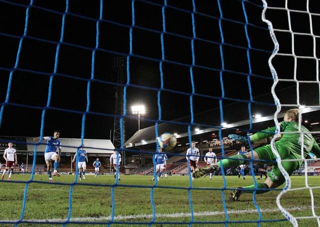Jonson Clarke-Harris of Peterborough United scores from the penalty spot past Cobblers 'keeper Jon Mitchell. Photo: Joe Dent/theposh.com.