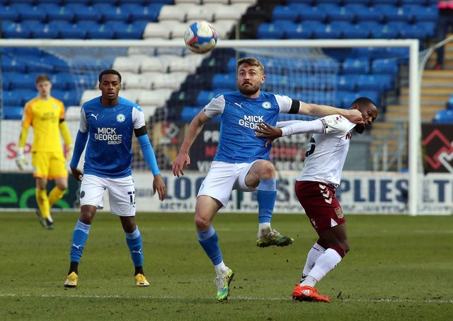 Dan Butler of Peterborough United battles with Mark Marshall of Northampton Town. Photo: Joe Dent/theposh.com.