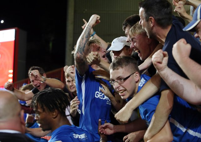 Jason Cummings is mobbed by Posh fans after scoring a late winner at Charlton.