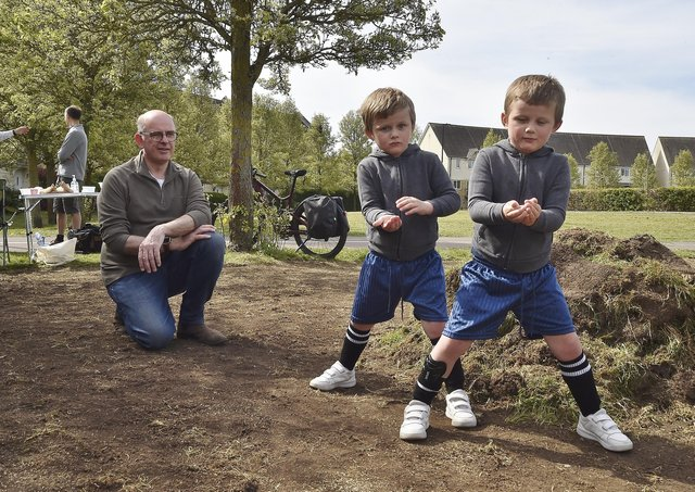 Seeding a community area at Sugar Way, Woodston are  Cllr Andy Coles with twins  Rex and Leo Greenaway (5). Picture: David Lowndes