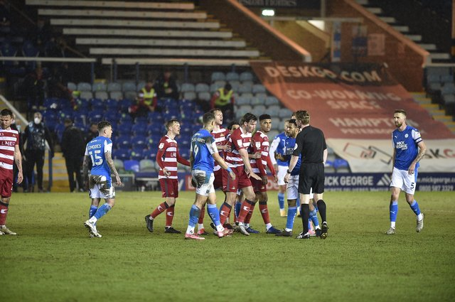 Doncaster players surround referee Scott Oldham demanding that Posh centre-back Frankie Kent is sent off late in the match. Photo: David Lowndes.