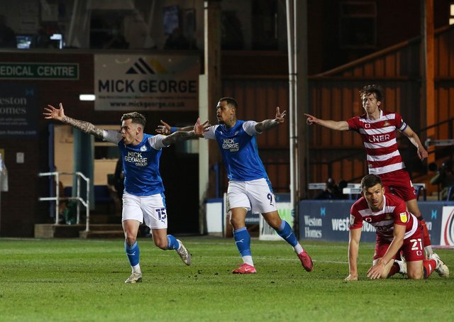 Sammie Szmodics and Jonson Clarke-Harris of Peterborough United appeal for a penalty in the match against Doncaster. Photo: Joe Dent/theposh.com.