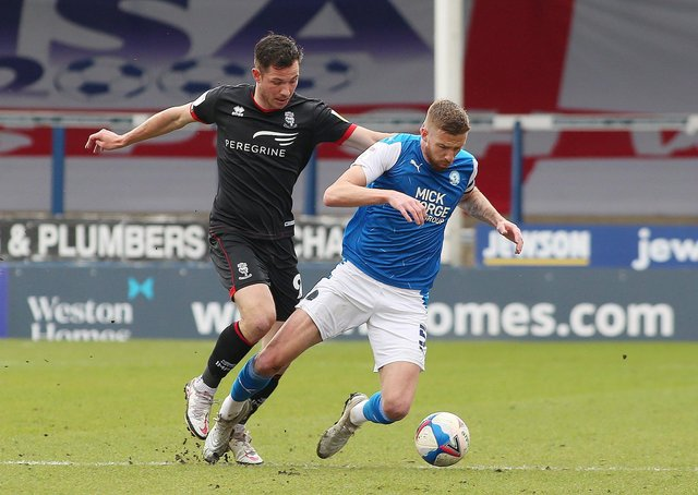 Mark Beevers of Peterborough United in action with Tom Hopper of Lincoln City. Photo: Joe Dent/theposh.com.