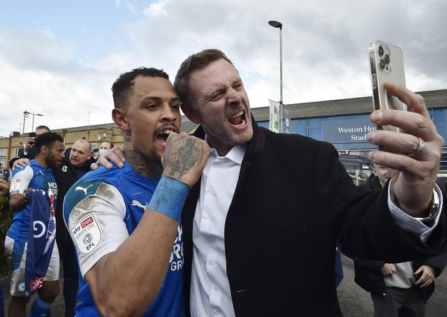 Jonson Clarke celebrates promotion with Posh co-owner Darragh MacAnthony. Photo: David Lowndes.