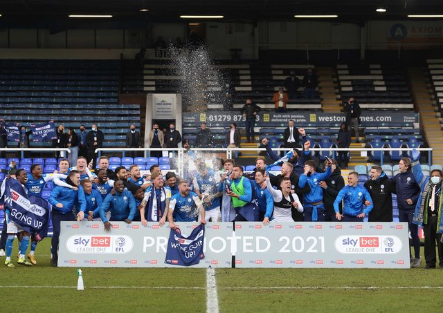 Posh players celebrate promotion to the Championship on the pitch after the thrilling 3-3 draw against Lincoln. Photo: Joe Dent/theposh.com.