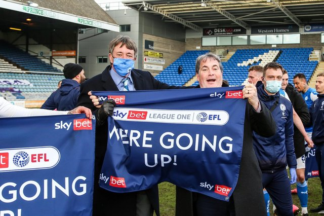 Posh co-owners Dr Jason Neale (left) and Stewart 'Randy' Thompson proudly hold the traditional promotion banner.