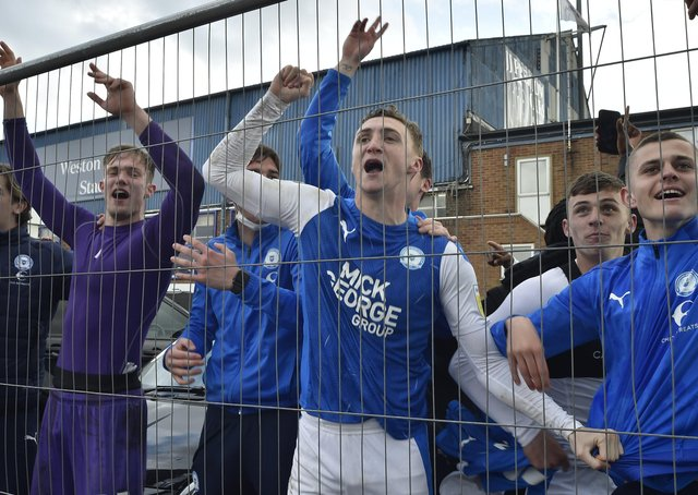 Posh players Jack Taylor (right) and Josef Bursik behind the wire fencing after winning promotion from League One. Photo: David Lowndes.