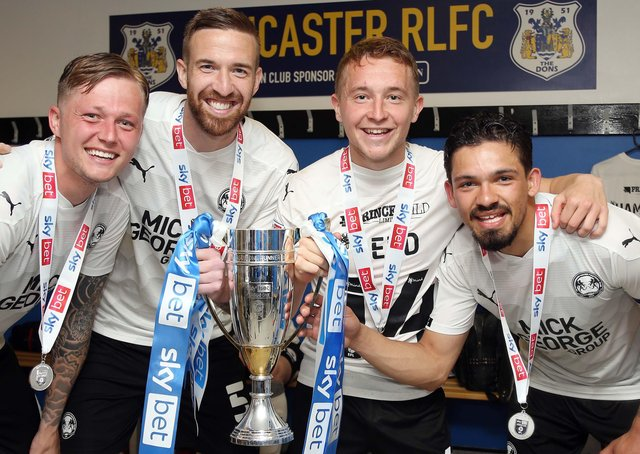 (from left) Frankie Kent, Mark Beevers, Louis Reed and Niall Mason with the League One runners-up trophy and their individual medals.