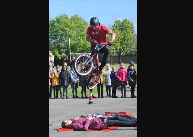 Mike Mullen performs a BMX jump over three members of staff.