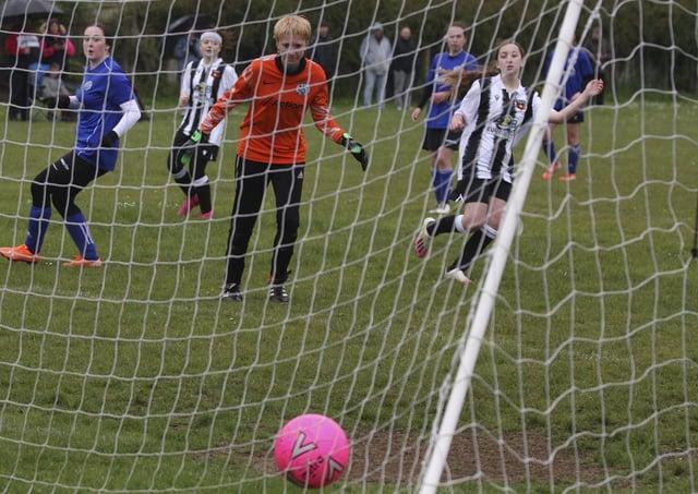 Libby Willis (stripes) scores for Peterborough Northern Star Under 16s v Cambridge City. Photo: Tim Symonds.