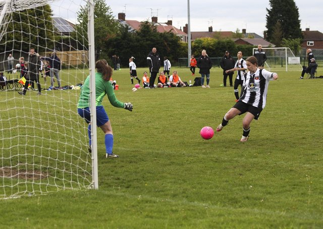 Libby Willis (stripes) scores for Peterborough Northern Star Under 16s against Saffron Walden. Photo: Tim Symonds.