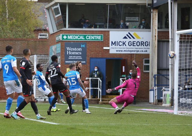 Siriki Dembele (blue, centre) scores for Posh against Lincoln.