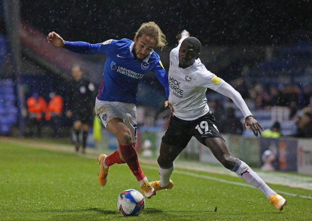 Idris Kanu of Peterborough United battles with Marcus Harness of Portsmouth at Fratton Park last season.