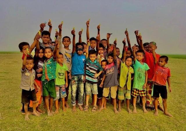School children in Bangladesh show off their Covid-19 wristbands.