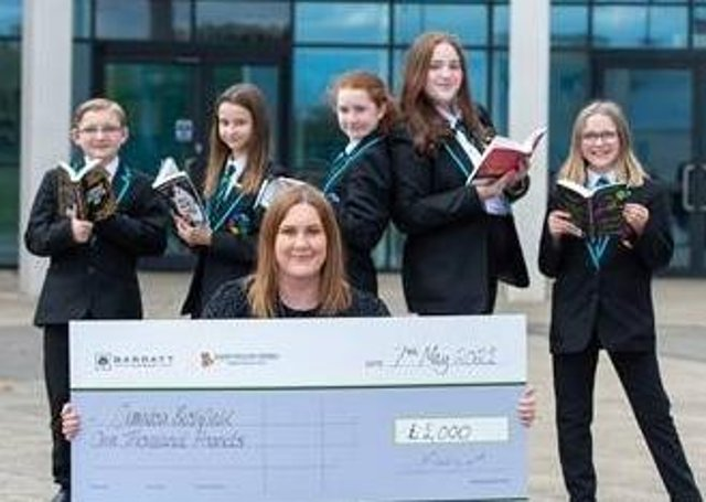 Students from Ormiston Bushfield Academy with the books donated from Barratt and David Wilson Home