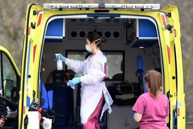 Staff wearing PPE of gloves and face masks, as a preactionary measure against COVID-19, disinfect an ambulance after it arrived with a patient at St Thomas' Hospital in north London (Photo: DANIEL LEAL-OLIVAS/AFP via Getty Images)